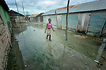 A girl walks through a flooded street in Batey Bombita, a community in the southwest of the Dominican Republic whose population is composed of Haitian immigrants and their descendents.