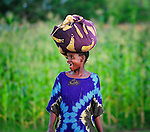 A woman laughs as she carries a bundle on her head as she walks through a cornfield in Karonga, a town in northern Malawi.