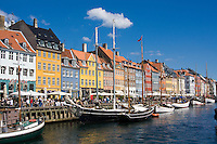 Crowds of people eating lunch at restaurants along Nyhavn or New Harbor canal in Copenhagen, Denmark.