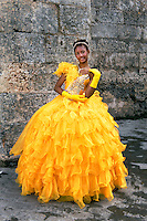 Fifteen-year-old girl posing in her Quinceanera dress   <br /> Havana, Cuba 2009.<br /> A young girl celebrates her fifteenth birthday as it marks her transition from childhood to womanhood. I was touched by the pride that each of these two people were feeling through their accomplishments. In one image this fifteen-year-old girl poses in her fluffy egg-yolk yellow Quinceanera dress, while just a few feet away, the fisherman has just caught a fish that he later told me fed his extended family for two nights.