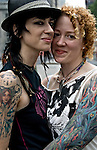 Half Length portrait of Punk Lesbian Couple with tattoos at the Dyke Parade, which goes  down 5th Avenue to Washington Square Park the day before the Gay and Lesbian Pride Parade.  Lesbian showing gender and sexual identity pride and orientation.