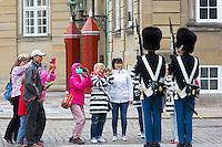 Tourists taking photograph of Royal Guard, in uniform at Royal Amalienborg Palace, Copenhagen, Denmark