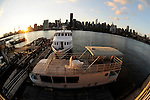 Bride and groom kiss at sunset on a ferry boat, on the East River, backed by  the Manhattan skyline.