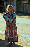 Central America, Latin America, Guatemala, Chichicastenango. A young girl waits for bus with baby on back.