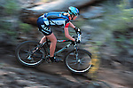 A woman competitor races her mountain bike down a narrow singletrack trail at the Lake Chelan Mountain Bike Festival in eastern Washington.