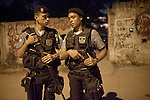 Police Pacification Unit (UPP) officer XXX Pinheiro, right, with an officer, patrols the streets in Complexo do Caju, a complex of a newly pacified favelas in the North Zone, Rio de Janeiro, Brazil, on Saturday, April 27, 2013. <br /> <br /> In the early hours of Sunday, March 3, 2013, about 1,400 Brazilian security forces occupied 13 communities during a joint public security operation to install a Pacifying Police Unit (UPP) in two Rio de Janeiro favelas, Complexo do Caju and Barreira do Vasco. Elite police units backed by armored military vehicles and helicopters invaded the neighborhood in an on-going policing program aimed to drive violent and heavily armed drug gangs out of Rio's poor communities, where the traffickers have ruled for decades. For the community of Caju, that is ADA (Amigos de Amigos).