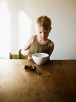 A young boy eating cereal in the morning sun with a toy gun on the table.