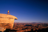 Mountain biker perched on White Crack Rock over looking Needles section Canyonlands National Park Moab Utah