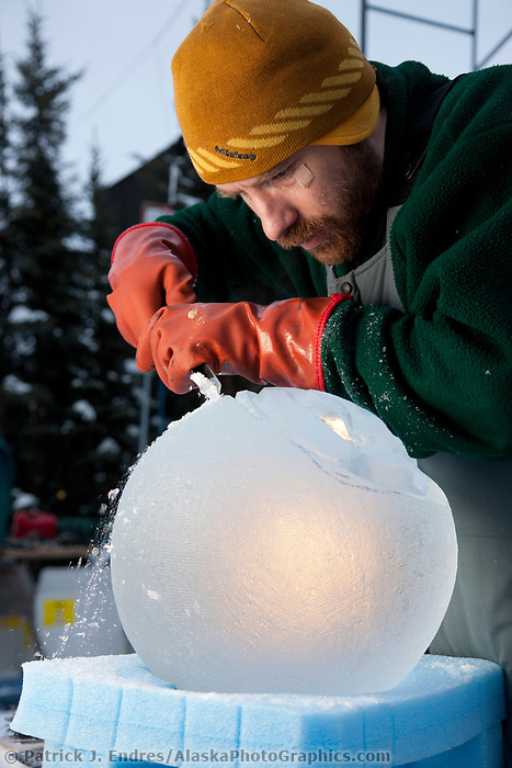 """Russian sculptor Vitaly Lednev, carves away on a single block, abstract sculpture titled """"Adam and Eve: One Heart for Two"""" during the 2009 World Ice Art Championships in Fairbanks, Alaska."""