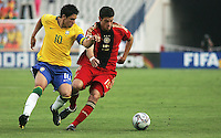 Germany's Semih Aydilek (15) is under pressure from Brazil's Giuliano (10) during the FIFA Under 20 World Cup Quarter-final match at the Cairo International Stadium in Cairo, Egypt, on October 10, 2009. Germany lost 2-1 in overtime play.
