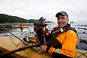 WA07081-00...WASHINGTON - Fishing from a kayak in the Straits of Juan De Fuca near Sail and Seal Rocks.