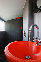The bathroom has been restored in a simple colour scheme of black, white and red with contemporary bathroom fittings