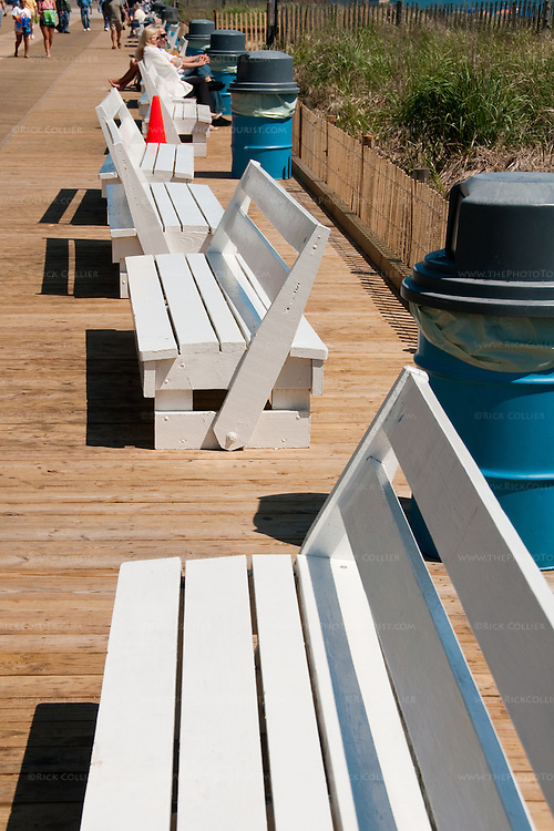 Freshly-painted benches with reversible backs line the beach side of the boardwalk at Rehoboth Beach, Delaware, as the boardwalk begins to fill up with visitors and beach-goers in the spring.