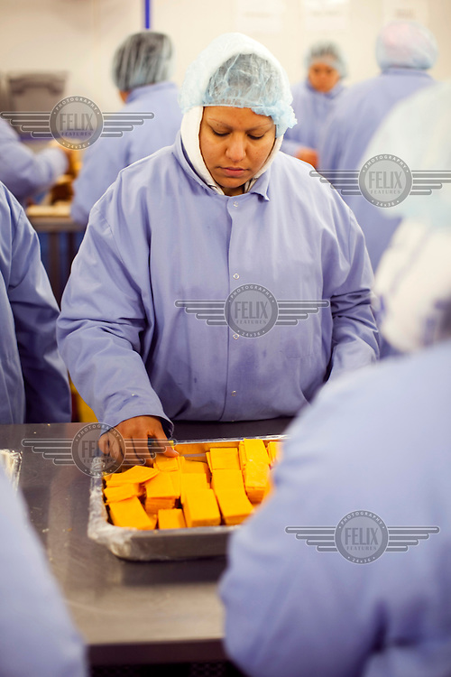 Workers, dressed in food hygiene workwear, at Greencore's Cincinnati facility add cheese slices to sandwiches. Greencore Group is an Irish-based company that produces convenience foods and sandwiches throughout Britain and Europe. In 2008 Greencore acquired Home Made Brand Foods in Newburyport, Massachusetts to establish Greencore North America.