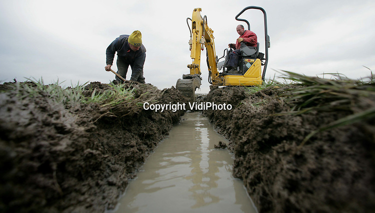 """Foto: VidiPhoto..VALBURG - Graven of verzuipen, is het motto van loonbedrijf Geert Rutjes uit het Gelderse Gendt. Zijn pas ingezaaide akker van 40 ha. met tarwe bij Valburg staat vol water. Oorzaak is de regenval van de laatste weken. De verzadigde vette Betuwse klei (""""het is net stopverf"""") kan het water niet meer verwerken. Vandaar dat Rutjes woensdag met graafmachine en schop aan de slag gaat om het vocht af te kunnen voeren. Diverse agrariërs hebben op de laaggelegen kleigronden met hetzelfde probleem te kampen."""