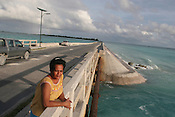 Beiataake Orea, a school teacher, stands on a man made causeway (with solar powered lighting)  which is the highest point above the sea, on the island of Kiribati as she contemplates waht the future holds for her low level island. The islands, and their way of life, are endangered by rising sea water levels which are eroding the fragile atoll, home to approximately 92,000 people.