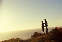 Couple stands together watching the sun set over the pacific ocean from the hills above