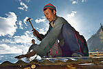 A man nails on tin roofing provided by the ACT Alliance as he puts the finishing touches on a transitional shelter in the Tamang village of Goljung, in the Rasuwa District of Nepal near the country's border with Tibet.<br /> <br /> In the aftermath of the April 2015 earthquake that ravaged Nepal, the ACT Alliance helped people in this village with a variety of services, including blankets, shelter and livelihood assistance.