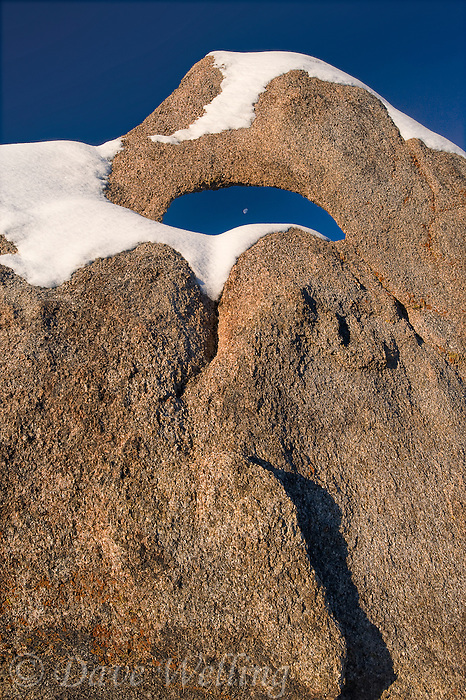 711700261 moonset through a snow covered granite arch winter in the eastern sierras seen from the alabama hills blm protected lands in kern county california