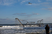 A media worker takes pictures of a roller coaster sitting next to the ocean, when the boardwalk it was built upon collapsed during Hurricane Sandy, in Seaside Heights, New Jersey, November 28, 2012.