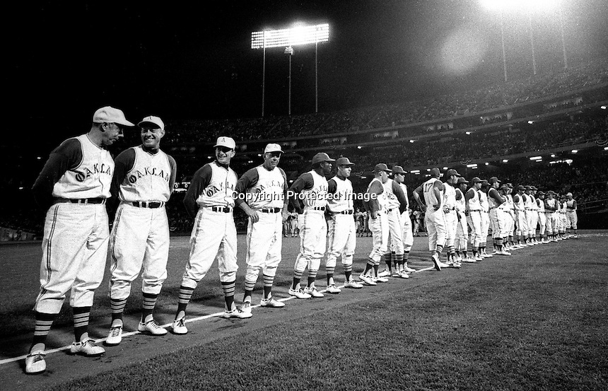 HISTORICAL NIGHT: The Oakland Athletics line up along the third baseline before their first home game at the Oakland-Alameda County Coliseum in Oakland, April 17, 1968. 50,164 fans along with Hall of Famer Joe DiMaggio (far left) were in attendence as the A's lost to the Baltimore Orioles 4-1. .(photo by Ron Riesterer/Oakland Tribune)