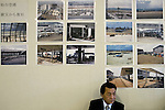A man sits in front of photos showing the devastation caused at the airport by the March 11 quake and tsunami that have been  displayed on a wall at Sendai airport in Natori, Miyagi Prefecture, Japan on 14 April, 2011. .Photographer: Robert Gilhooly