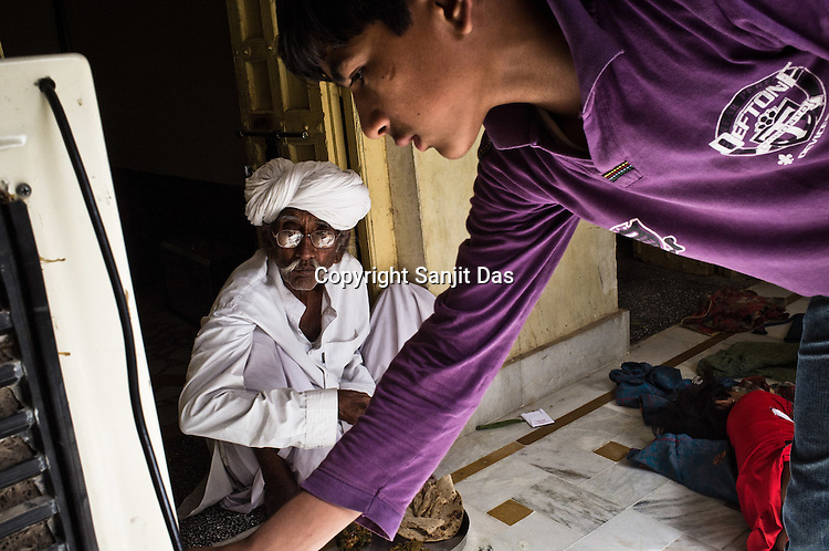 75-year-old Manganiyar artist sits down to eat his lunch and his grandson is seen helping with the aircooler inside their house in Hamira village of Jaiselmer district in Rajasthan, India. Photo: Sanjit Das/Panos