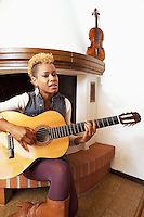 Switzerland. Canton Ticino. Aranno. Orpheline at home. Orpheline is a composer, song writer, a singer and a musician. She sings and plays the guitar. She is a young woman (24 years old). Her mother is swiss and her father was a black american citizen. Mixed race. Aranno is located in the Malcantone area. 19.03.2010 © 2010 Didier Ruef