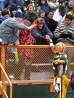 Green Bay Packers safety Eugene Robinson gives the game ball to a fan after he intercepted a pass in the December 1, 1996 game against the Chicago Bears. The Pack won the game, 28-17.