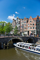 Tourist boat takes tour cruise group sightseeing on Dutch canals, Prinsengracht and Brouwersgracht , Amsterdam, Holland