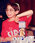 WATERBURY, CT 12/13/98 --1213JH06.tif--Matthew Perreault, 9, of Waterbury had to struggle a bit to open the box of wooden blocks he got as a gift during the celebration of the first night of Hanukah Sunday evening at Beth El  Synagogue in Waterbury. The members of the synagogue were joined by members of B'nai Shalom for the celebration, which featured the lighting of the candles, eating  latkes, and exchanging gifts. Each family also brough a gift for the intefaith ministries toy sale. JOHN HARVEY staff photo STANDALONE PHOTO.