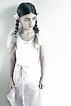 Female youth with plaited hair looking to side with sad expression
