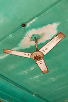 A rusting vintage fan is suspended from a water-stained ceiling