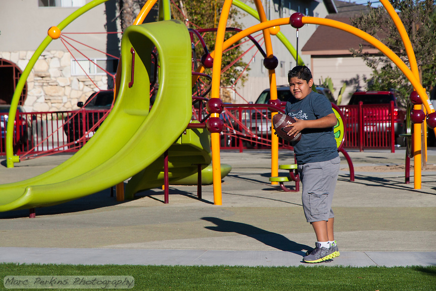 A boy prepares to throw a football in front of a play structure at Circle Park, a pocket park located on Park Circle Drive in Anaheim, California.