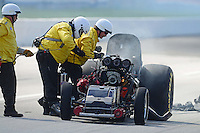 Sept 9, 2012; Clermont, IN, USA: NHRA safety safari crews tend to funny car driver Todd Lesenko after he blew the body off his car in a fiery explosion during the US Nationals at Lucas Oil Raceway. Mandatory Credit: Mark J. Rebilas-