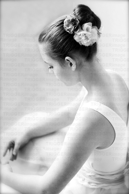 Close up of a young girl sitting in ballet costume with flowers in her hair