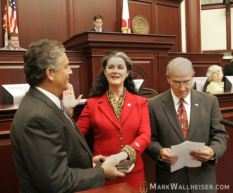 """Represenative Marty Bowen, center, from Haines City, looks at her husband, Brian Barnard, of Tallahassee, holding the Bible as she takes the oath of office of Speaker Pro-Tempore being administered by William """"Bo"""" Pittman lll, right, the Chief Clerk of the House during the legislative special session called to deal with the issue of  tax relief at the Florida Capitol in Tallahassee, Florida June 12, 2007.  Both the House and Senate met for less than 30 minutes before adjourning.  (Mark Wallheiser/TallahasseeStock.com)"""