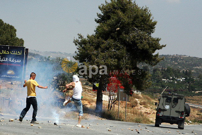 A Palestinian youth kicks tear gas canister fired by Israeli soldiers during clashes in the West  Bank village of Nabi Saleh, on 28 May 2010. Palestinians protest weekly against the neighbouring Jewish settlement of Halamish. photo by Eyad Jadallah
