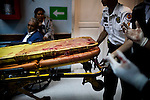 "Paramedics push a blood-soaked gurney from a shooting victim at Roosevelt Hospital in Guatemala City, on Saturday, May 5, 2012. The police named the victim, who was a truck driver, ""dos equis"", or dbl XX (meaning, without name) because he carried no identification. The police sprayed his truck and shot the driver when he did not stop at a checkpoint."