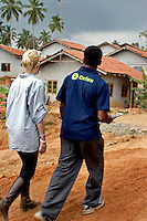 Scarlett tours a village on the south coast an Oxfam project has built a water drainage system and septic tanks for 100 hundred government houses in a flood prone area. The inhabitants previous houses were destroyed by the Tsunami.