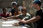 Three East Timorese men are detained by Portugese Police (GNR) after having a weapon, a viscous looking club with nails, found in their possession. The police set up a roadblock in Bairo Pitie, a area in Dili notorious for gang violence, after a clash involving stone throwing gang members and incidents of arson where a number of houses were set on fire.