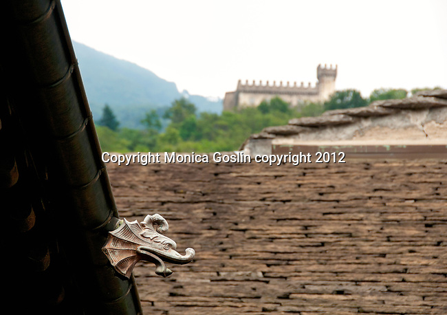 A gargoyle on the roof of Town Hall with Sasso Corbaro castle in the distance in Bellinzona, Switzerland