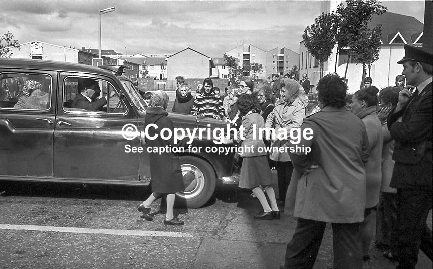 A taxi is held up by women & children blocking the Shankill Road, Belfast, N Ireland. The protest was against lawless elements burning the buses that served the area. September 1976. 197609000485a..Copyright Image from Victor Patterson, 54 Dorchester Park, Belfast, UK, BT9 6RJ..Tel: +44 28 9066 1296.Mob: +44 7802 353836.Voicemail +44 20 8816 7153.Skype: victorpattersonbelfast.Email: victorpatterson@me.com.Email: victorpatterson@ireland.com (back-up)..IMPORTANT: If you wish to use this image or any other of my images please go to www.victorpatterson.com and click on the Terms & Conditions. Then contact me by email or phone with the reference number(s) of the image(s) concerned.