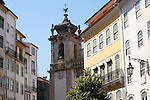 A street in Coimbra, Portugal with a church tower in the background.