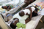 A woman sleeps with her child, who is sick with cholera, at the Hospital Albert Schweitzer on Friday, October 29, 2010 in Deschapelles, Haiti.
