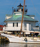 Chesapeake Bay Maritime Museum, St. Michaels, Maryland<br /> Hooper Strait Lighthouse (1879) stands behind the skipjack sloop HM Krent on Navy Point