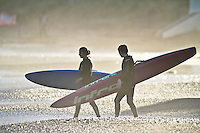 Two board paddlers walk down to the waters edge during a late afternoon training session at Lyall Bay.
