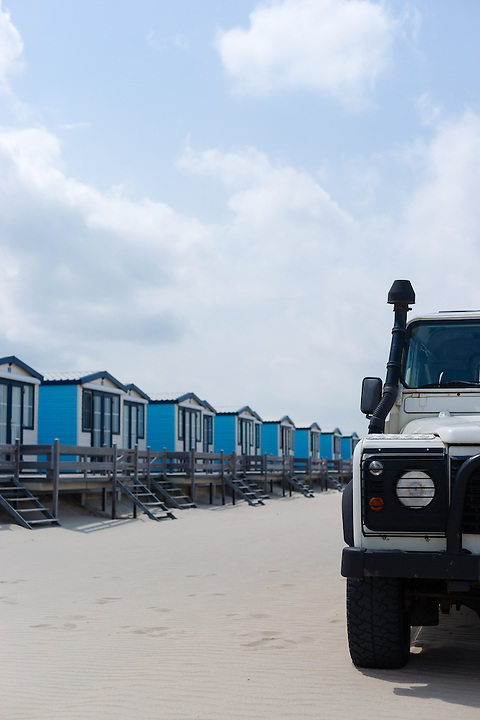 Blue cabanas for rent on a sandy beach with a 4x4 in the foreground