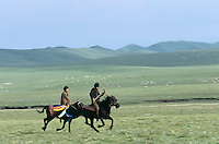 Outside Labrang near Gwasi - Tibetan nomad men horse racing for summer mountain festival.