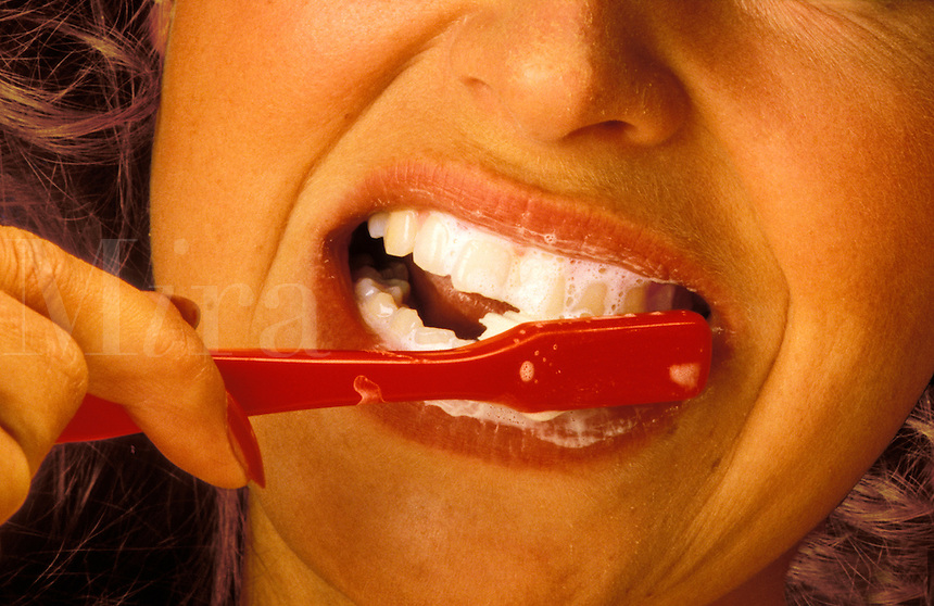 Young woman cleaning her teeth. Close up